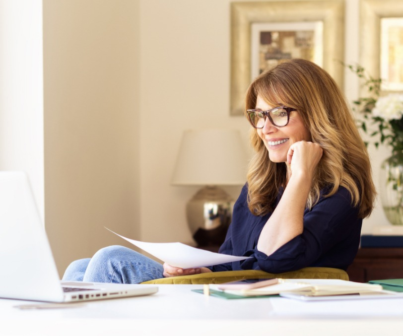 Attractive mature woman sitting at desk and using laptop while working at home